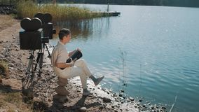 Movie director in hair net eat grapes from speaker on lake shore with two camera stock footage