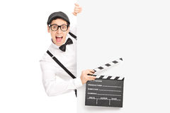 Movie director holding clapperboard behind a panel Royalty Free Stock Image