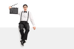 Movie director holding clapperboard seated on a panel Royalty Free Stock Photo