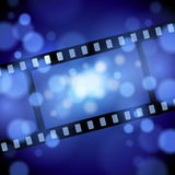 Movie Film Background. A film reel strip movie image background with a dark and bright blue light shining vector illustration