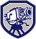 Movie Film Camera Vintage Shield. Illustration of a vintage movie film camera viewed from low angle front set inside shield crest shape done in retro  style Royalty Free Stock Photography