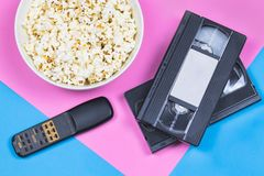White bowl of popcorn, 2 VHS tapes and old fashioned remote control on a bright pink and blue background. royalty free stock photography