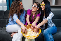 Movie with the girls. Fun Movie with Girlfriends. Three smiling girls eating popcorn while watching a movie on tv at home Stock Photography