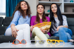 Movie with the girls. Fun Movie with Girlfriends. Three smiling girls eating popcorn while watching a movie on tv at home Stock Image