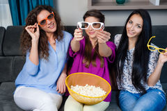 Movie with the girls. Fun Movie with Girlfriends. Three smiling girls eating popcorn while watching a movie on tv at home Royalty Free Stock Image