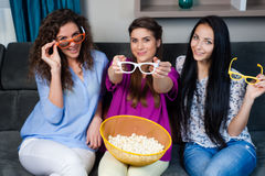 Movie with the girls. Fun Movie with Girlfriends. Three smiling girls eating popcorn while watching a movie on tv at home Stock Photos
