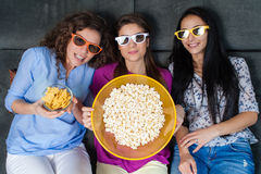 Movie with the girls. Fun Movie with Girlfriends. Three smiling girls eating popcorn while watching a movie on tv at home Royalty Free Stock Photos