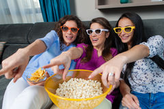 Movie with the girls. Fun Movie with Girlfriends. Three smiling girls eating popcorn while watching a movie on tv at home Royalty Free Stock Photo