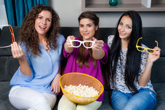 Movie with the girls. Fun Movie with Girlfriends. Three smiling girls eating popcorn while watching a movie on tv at home Royalty Free Stock Images