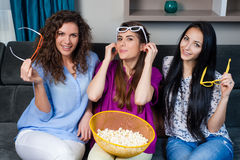 Movie with the girls. Fun Movie with Girlfriends. Three smiling girls eating popcorn while watching a movie on tv at home Royalty Free Stock Photography