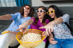 Movie with the girls. Fun Movie with Girlfriends. Three smiling girls eating popcorn while watching a movie on tv at home Stock Photo