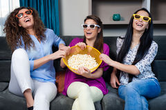 Movie with the girls. Fun Movie with Girlfriends. Three smiling girls fighting on popcorn while watching a movie on tv with 3d glasses, at home, eating popcorn Stock Images