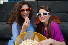 Movie with the girls. Fun Movie with Girlfriends. Two smiling girls eating popcorn while watching a movie on tv with 3d glasses, at home Royalty Free Stock Photo