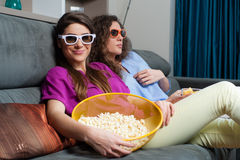 Movie with the girls. Fun Movie with Girlfriends. Two smiling girls eating popcorn while watching a movie on tv with 3d glasses, at home Royalty Free Stock Image