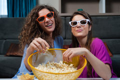 Movie with the girls. Fun Movie with Girlfriends. Two smiling girls eating popcorn while watching a movie on tv with 3d glasses, at home Stock Photography