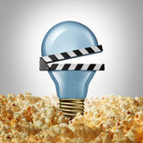 Movie Idea. Concept and cinema creativity symbol as a light bulb or lightbulb in popcorn shaped as an open clap board or video slate as a metaphor for finding Stock Photo