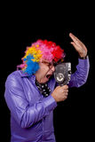 Movie maker. Man with rainbow afro wig recording a movie with retro film camera Royalty Free Stock Image