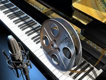 Movie Music. A film roll on the keyboard of a piano, and a studio microphone, symbolising the movie music, soundtracks or scores Royalty Free Stock Photography