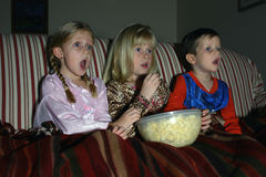 Movie Night. Sisters and brother share a bowl of popcorn on a couch under a cozy blanket