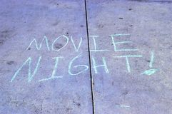 Movie Night Advertisement. A chalk writing advertising Movie Night on a city sidewalk. aqua blue chalk making a statement royalty free stock images