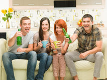Movie night with friends. Portrait of four young caucasian friends sitting on sofa holding drinks, watching a television show Royalty Free Stock Photo