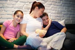 Single Mother And Children Watching TV At Night. Movie night at home with divorced mother, daughter and son. Modern family watching television and eating popcorn Stock Photos