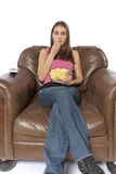 Movie night relaxing watching TV eating popcorn. Young woman sits in an over sized leather chair relaxing and eating popcorn facing forward. This could be retro Royalty Free Stock Images