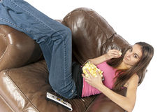 Movie night relaxing watching TV eating popcorn. Tilted view or rotated view of young woman sitting in an over sized leather chair sideways with legs across the Stock Photo