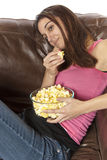 Movie night relaxing watching TV eating popcorn. Young woman sits in an over sized leather chair relaxing and eating popcorn. Head laying on back of couch. This Royalty Free Stock Photography