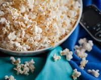 Movie night with remote, popcorn bowl and blanket. royalty free stock images