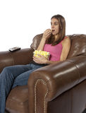 Movie night watching TV eating popcorn. Young woman sits in an over sized leather chair relaxing and eating popcorn facing to left. This could be retro of the Royalty Free Stock Image