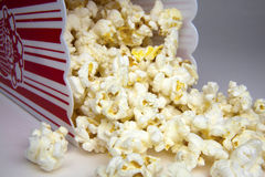Movie Popcorn. Popcorn container on its side with popcorn kernals spilling out stock photos