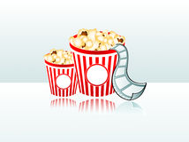 Movie popcorn film strip. Two popcorn buckets with film strip reflected on glass table Royalty Free Stock Photography