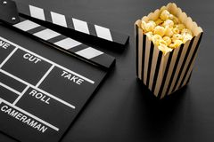 Movie premiere concept. Clapperboard and popcorn on black background royalty free stock images