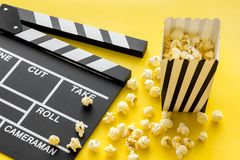 Movie premiere concept. Clapperboard and popcorn on yellow background royalty free stock images