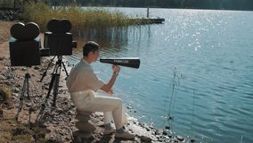 Movie producer in hair net eat grapes from speaker on lake shore with two camera. Movie producerin hair net and white clothes eat grapes from speaker on lake stock video