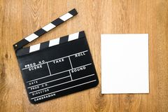 Movie production clapper. Board with empty paper against wooden background Royalty Free Stock Image