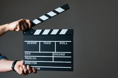 Hands with a movie clapperboard. A movie production clapper board. Hands with a movie clapperboard on grey background with copy space, close-up Royalty Free Stock Images