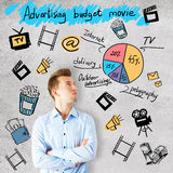 Movie production concept. Handsome young businessman on concrete background with cinematography related drawings. Movie production concept royalty free stock photography