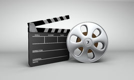 Movie reel & Clapboard. A slate clapboard and film reel with film setting next to each other Stock Images