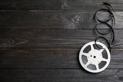 Movie reel on wooden background. Cinema production. Movie reel on wooden background, top view with space for text. Cinema production stock photo