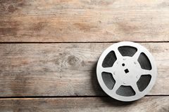 Movie reel on wooden background, top view. Cinema production. Movie reel on wooden background, top view with space for text. Cinema production stock photo