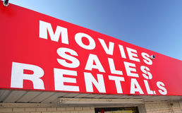 Movie Rental Sign on Convenience Store. With Blue Sky Stock Photo