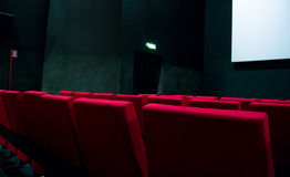 Movie screen and red chairs inside of a cinema.  Stock Photography