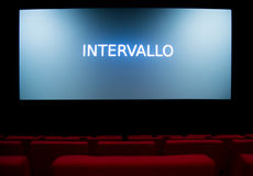 Movie screen and red chairs inside of a cinema Stock Images