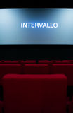 Movie screen and red chairs inside of a cinema Royalty Free Stock Image