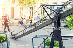 Movie set with professional equipment and media production team on city street. Outdoor film making. Big camera crane with stock photography