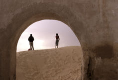 Movie set- Tunisia. Tourists framed by ruin of building built for the set of Star Wars Phantom Menace in the remote Saharan country near the Grand Sud- Tunisia Royalty Free Stock Image