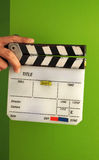 Movie slate board or clapper board and man hand. Movie slate board or clapper board and man hand and white color and green screen background in studio Royalty Free Stock Photo
