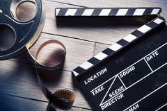 Movie slate and film reel on wood. Movie clapper and film reel on a wooden backgorund